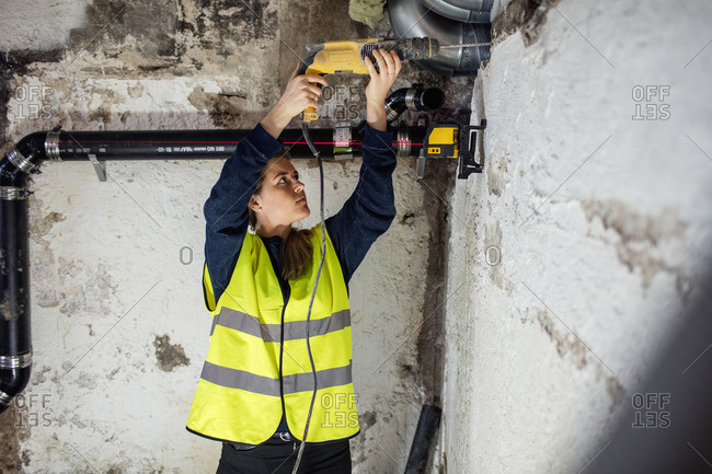 Confident woman drilling on wall above pipes at basement