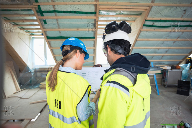 Rear view of male and female experts discussing at construction site