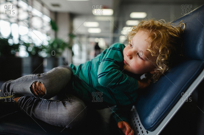 Boy lying down on a chair in an airport lobby