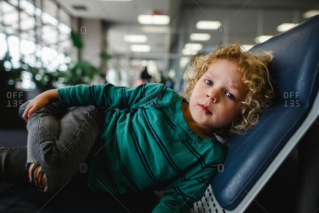 Boy reclining on a chair in an airport lobby