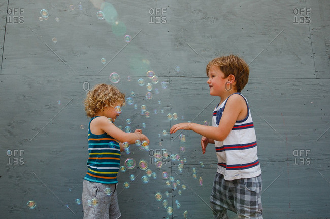 Two boys playing outdoors with bubbles