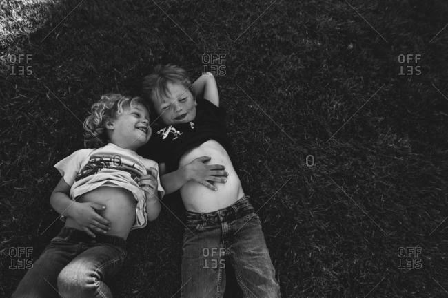 Two boys lying down together on the grass