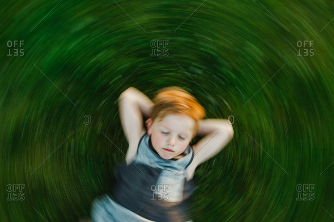 Overhead view of a boy lying down on the grass spinning