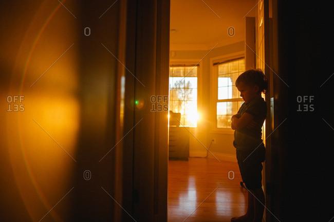 Boy standing defiantly in a doorway to his bedroom