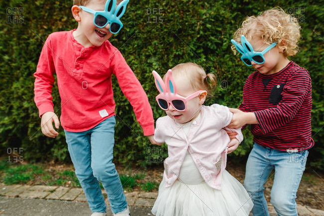 Three children wearing bunny rabbit sunglasses and playing outside