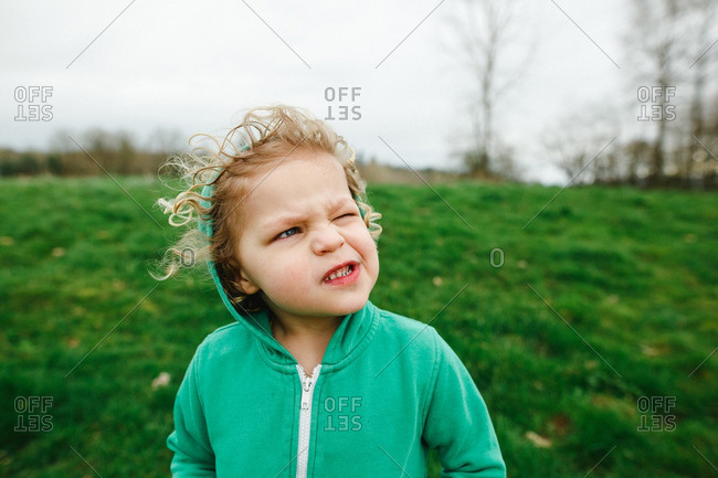 Child wearing a hooded sweatshirt outside on a windy day