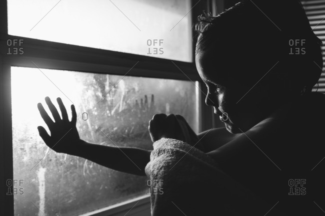 Child reaching out to touch a window