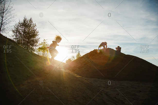 Children playing on a hillside at sunset