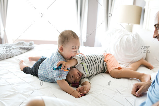 Brothers wrestling together on a bed