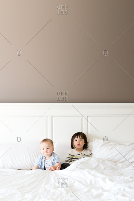 Two brothers sitting against a headboard on a bed