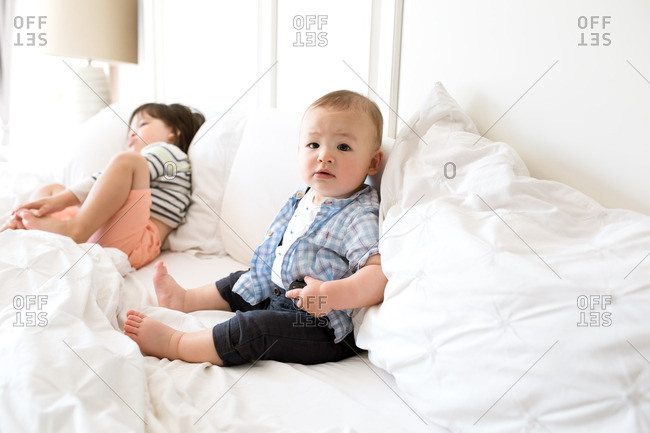 Two brothers leaning against white pillows on a bed
