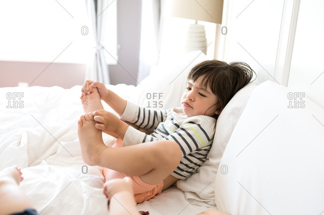 Little boy leaning against white pillows on a bed