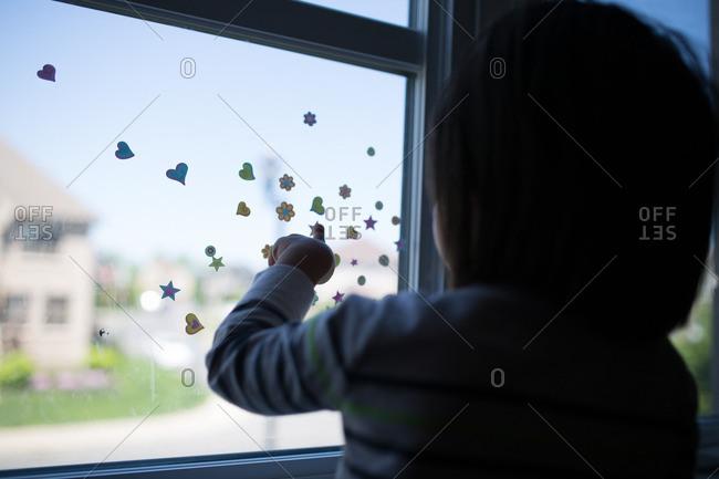 Little boy touching stickers on a window