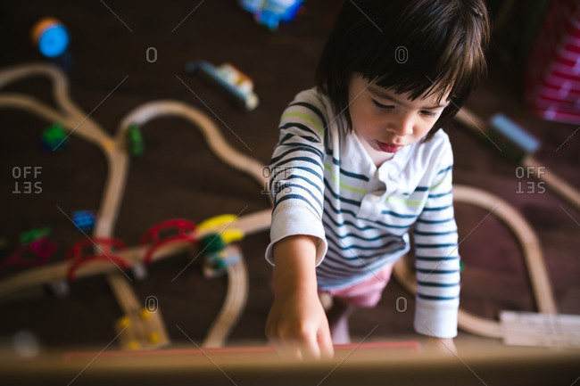 Boy standing at an easel over a toy train set