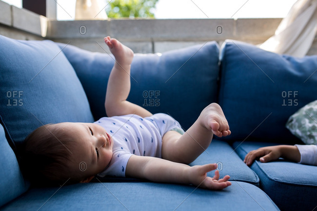 Toddler boy lying on an outdoor sofa