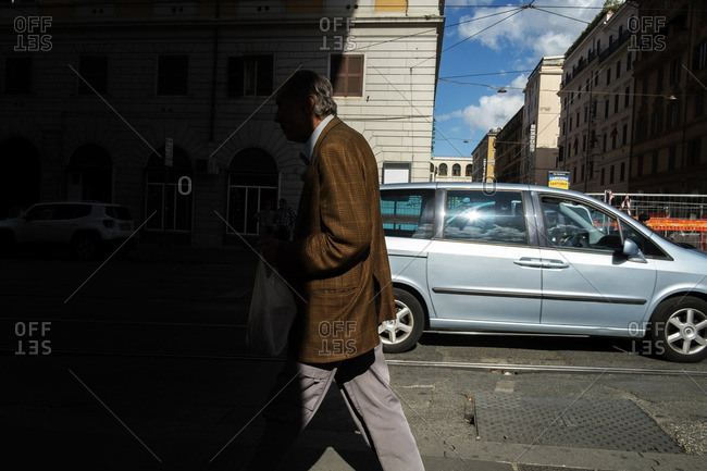 Rome, Italy - October 15, 2016: Man walking into shadow on street