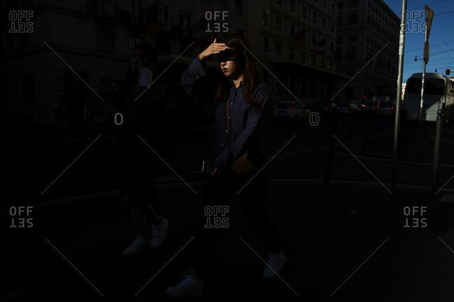 Woman shielding face walking in street