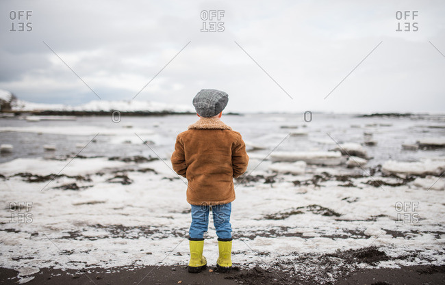 Boy standing on a frozen shoreline