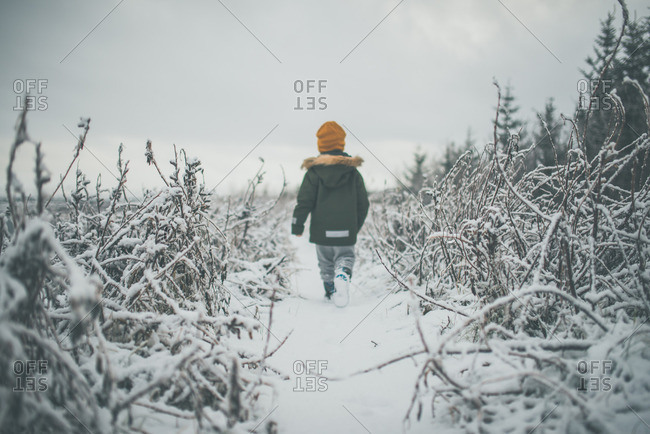 Child walking down a snowy trail alone
