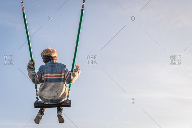 Child swinging on a clear sunny day