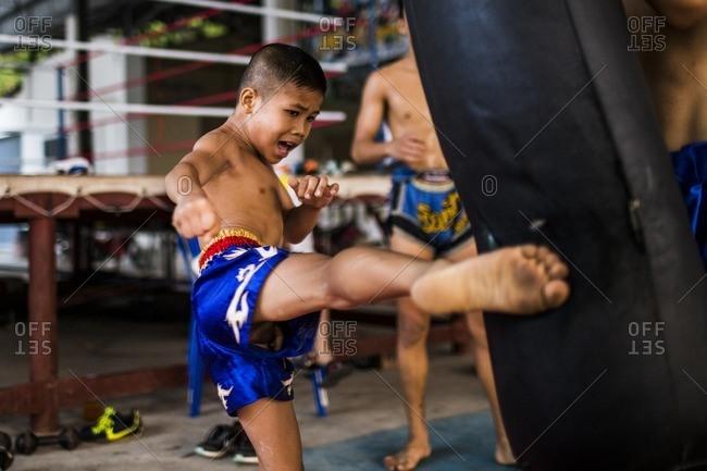 Rayong, Thailand - February 24, 2016: Boy kicking punching bag in Muay Thai training