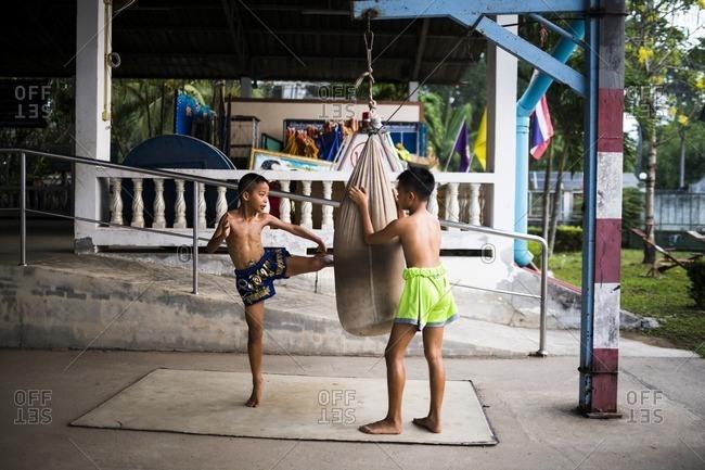 Rayong, Thailand - February 24, 2016: Boy kicking bag in Muay Thai training