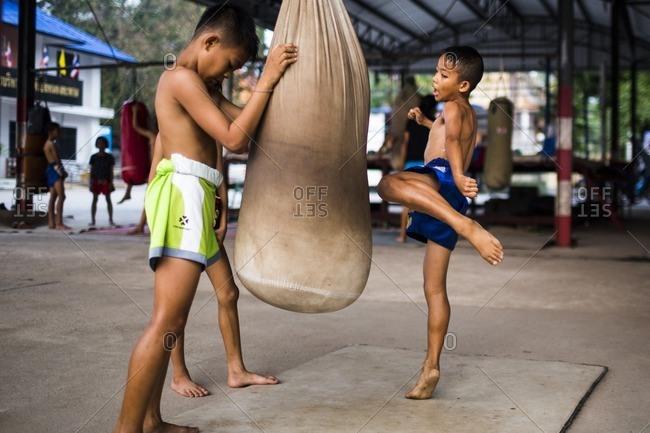 Rayong, Thailand - February 24, 2016: Boy kicking a bag in Muay Thai training