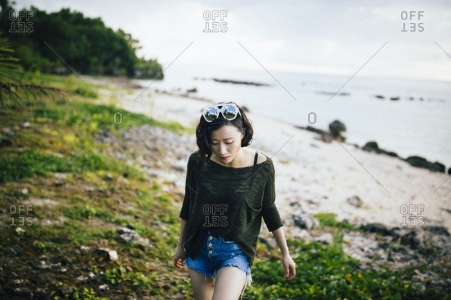 Guam, Mariana Islands - July 28, 2016: A young woman at a secluded beach