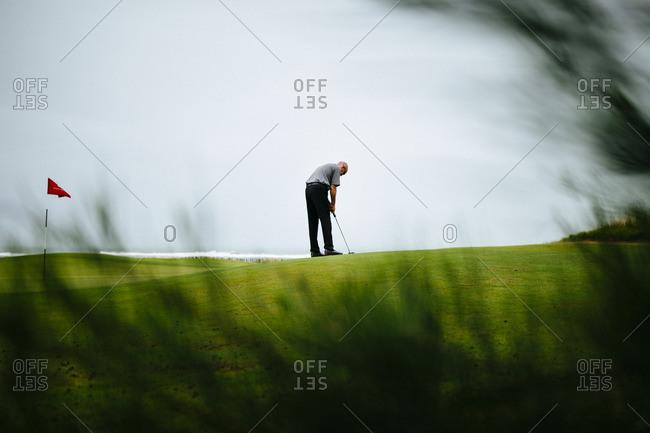 Danang, Vietnam - September 22, 2016: Golfer plays the green by ocean