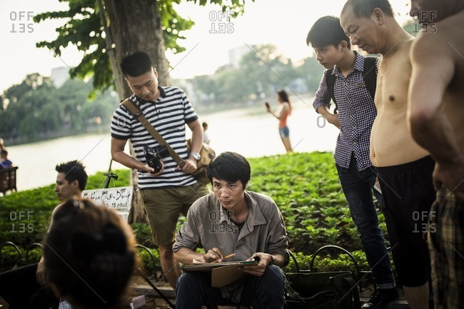 Hanoi, Vietnam - September 25, 2016: Artist drawing portrait at Hoan Kiem Lake