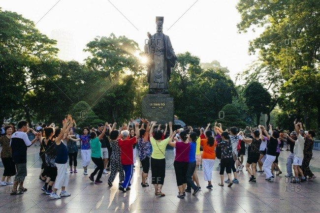 Hanoi, Vietnam - September 26, 2016: Morning yoga around a statue