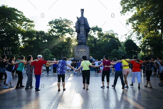 Hanoi, Vietnam - September 26, 2016: Morning yoga beneath a statue