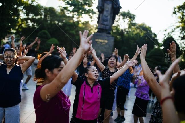 Hanoi, Vietnam - September 26, 2016: Morning yoga around park statue