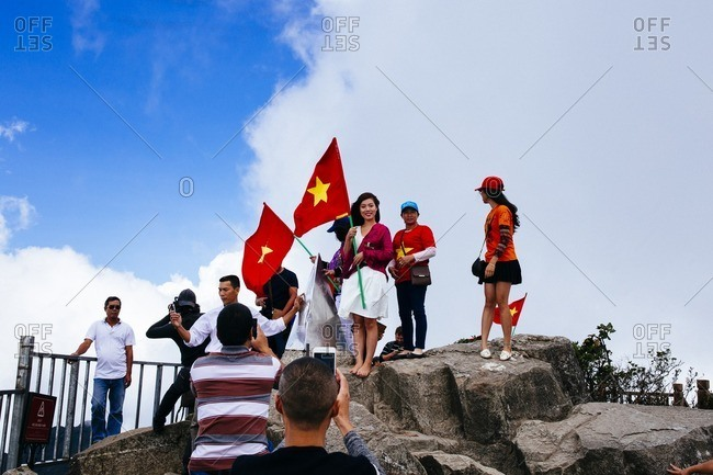 Sapa, Vietnam - September 28, 2016: People with flags at top of Mount Fansipan