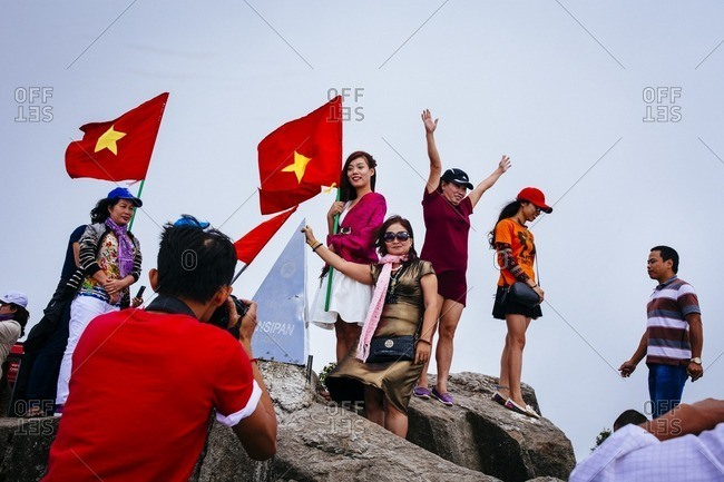 Sapa, Vietnam - September 28, 2016: People with flags on top of Mount Fansipan