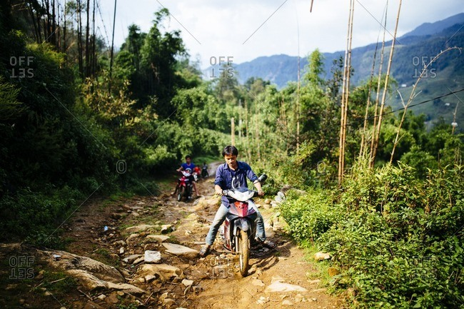 Sapa, Vietnam - September 28, 2016: Young men ride motorbikes up mountain path