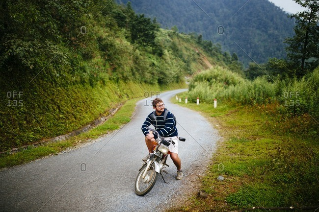 Sapa, Vietnam - September 28, 2016: A man rests on motorbike in mountains