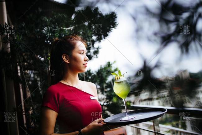 Ho Chi Minh City, Vietnam - September 30, 2016: Hotel bar waitress with tray