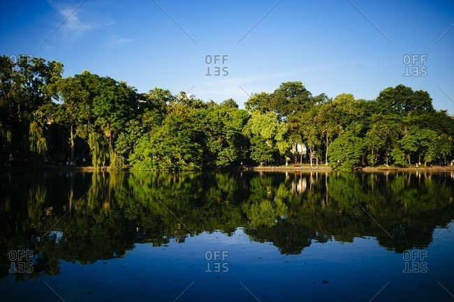 Trees and blue sky reflected on Hoan Kiem Lake