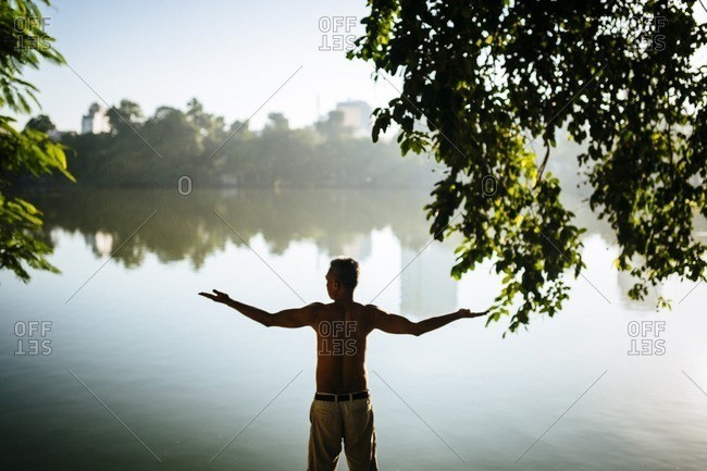 Man with raised arms on Hoam Kiem Lake