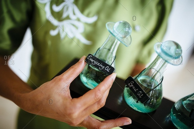 Hand with bottles of massage oil