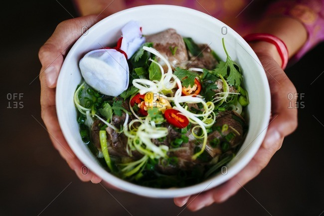 Hand holding bowl of beef pho