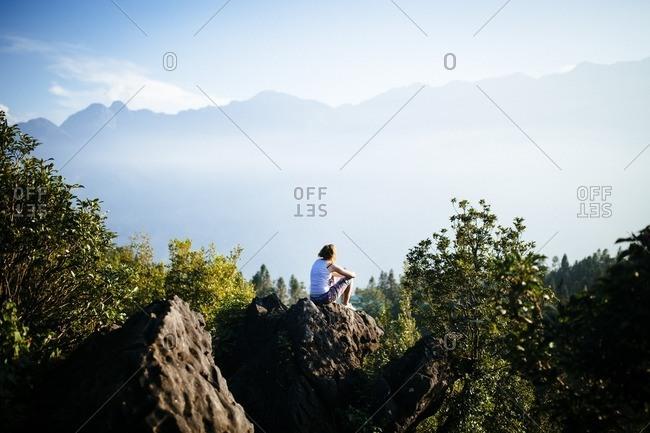 Woman overlooks a mountainous landscape, Sapa, Vietnam