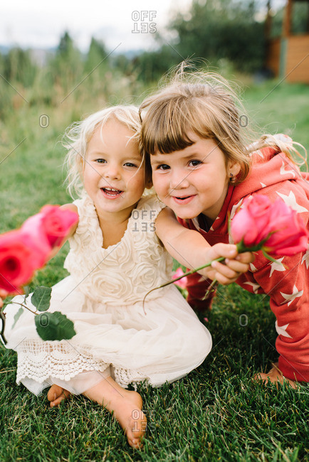 Smiling girls with roses in country