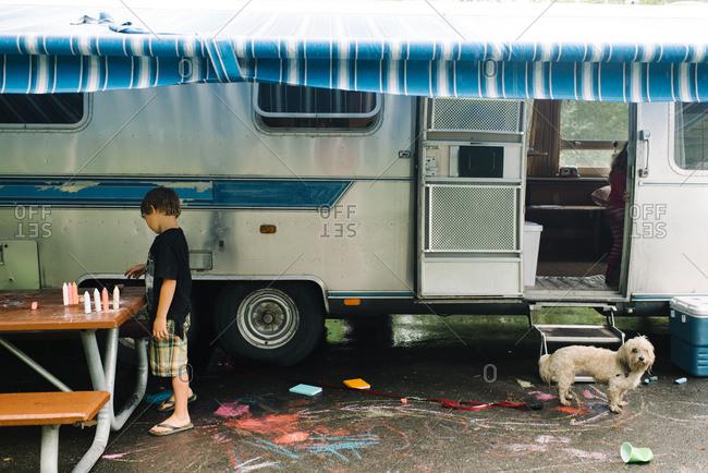 Boy arranging chalk under camper awning