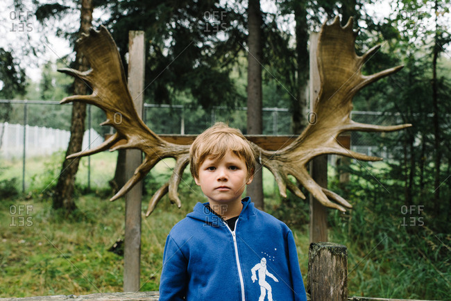 Boy in front of moose antlers