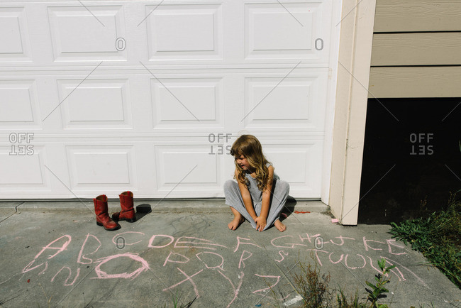 Girl drawing letters with chalk