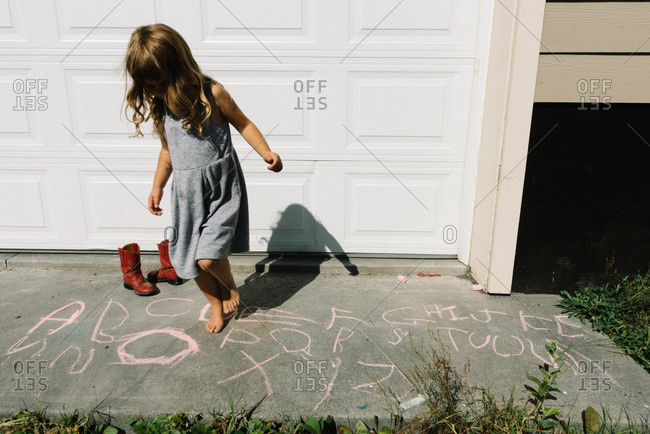 Girl by letters drawn with sidewalk chalk