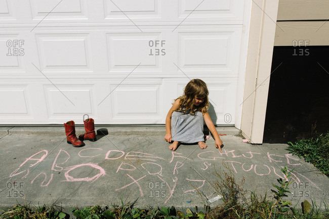 Girl drawing letters with sidewalk chalk