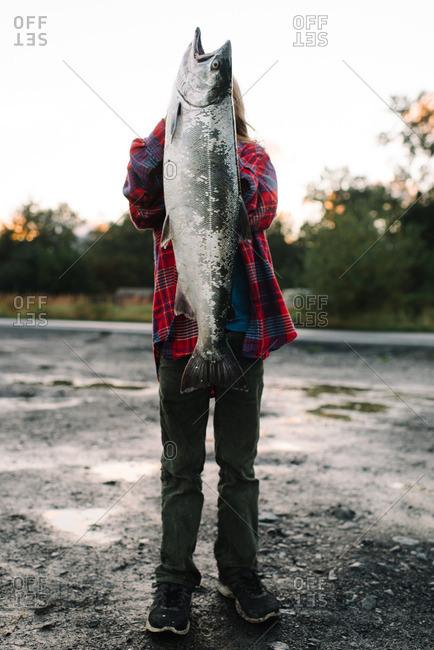 Boy holding up large salmon